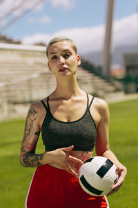 Female footballer holding a ball on the field