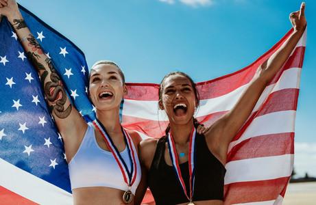 Female athletes celebrating victory holding american flag