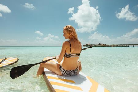 Woman enjoying paddleboarding at a beach