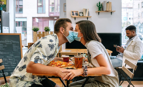 Couple kissing with mask sitting in a restaurant