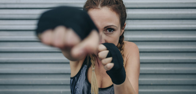 Sportswoman looking at camera and punching