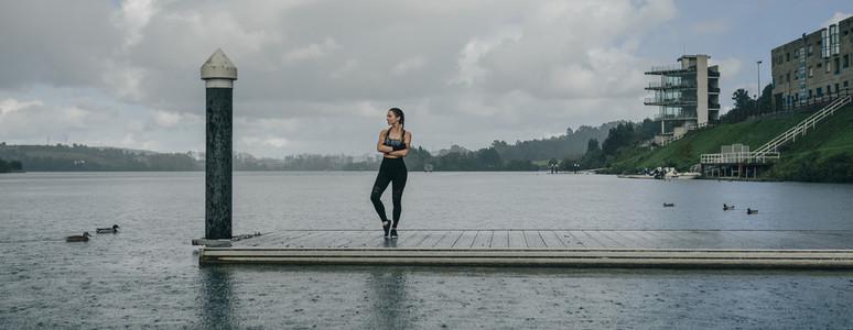 Sportswoman looking lake from pier