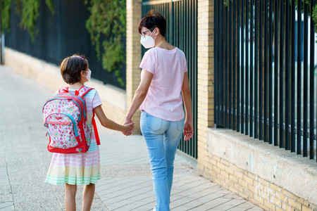 Nine years old girl with bag walking with her mother hand in hand