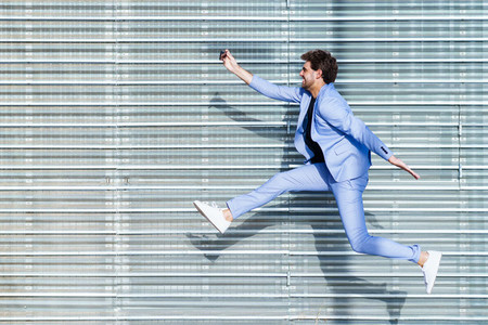 Man wearing a suit makes a selfie with a smartphone while jumping