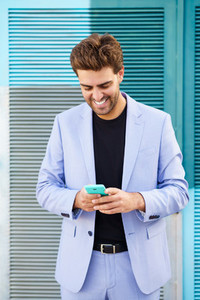 Smiling man wearing blue suit texting with a smartphone outdoors