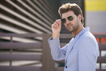Young handsome man wearing sunglasses in urban background