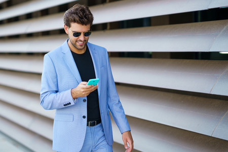 Man walking down the street using his smartphone with a happy expression