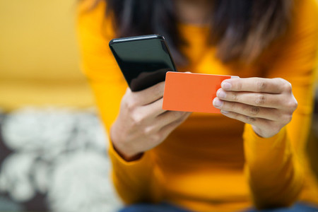 Woman shopping with smartphone paying with her credit card