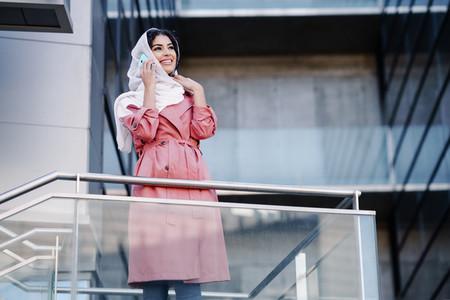 Young Muslim woman wearing hijab using her smartphone