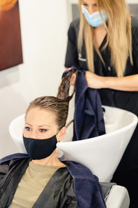 Female hairdresser washing a clients head in a salon  protected by a mask
