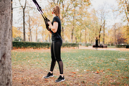 Women training with trx outside in the park
