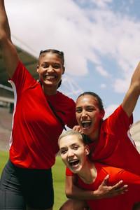 Female soccer team celebrating a victory