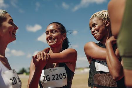 Women runners doing warmup exercises at the stadium