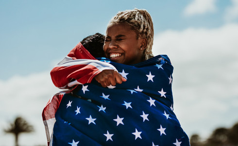 American female athletes with flag hugging each other after a wi