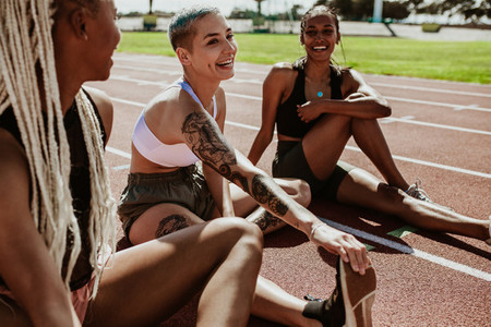 Athletes relaxing after running workout at stadium track