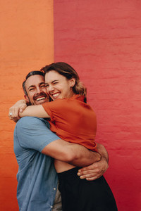 Loving couple embracing against colored wall