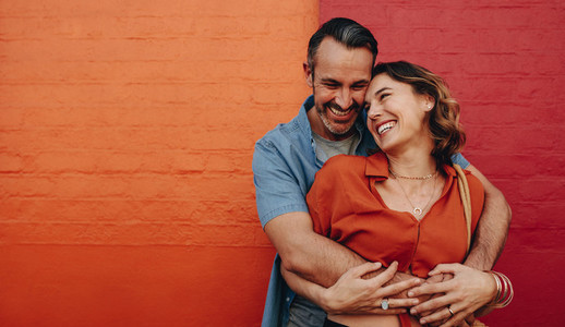 Romantic couple together on multicolored wall