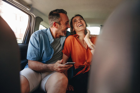 Loving couple having fun in the backseat of a car