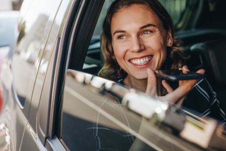 Businesswoman making phone call in car