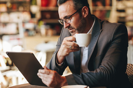 Business professional using digital tablet at coffee shop