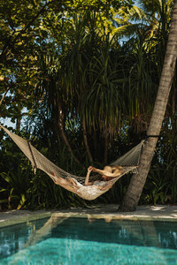 Woman relaxing in a hammock at a beach resort