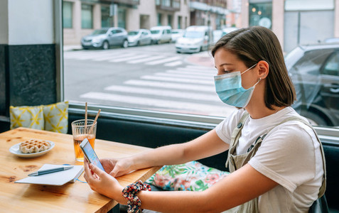 Woman with mask having a snack in a coffee shop