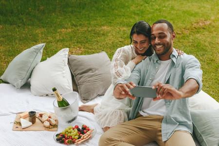 Loving couple taking selfie on picnic