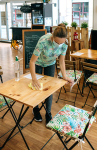 Waitress disinfecting tables in a coffee shop