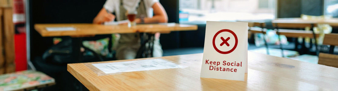 Coffee shop table with do not use sign with girl in background