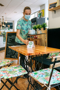 Waitress placing sign on coffee shop tables