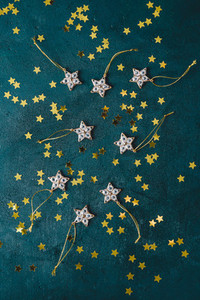 The New Year or Christmas festive flat lay with golden stars over a dark green background