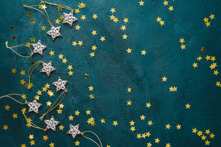 The New Year or Christmas festive flat lay with golden stars over a dark green background Top view copy space