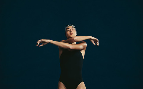 Female swimmer stretching arms