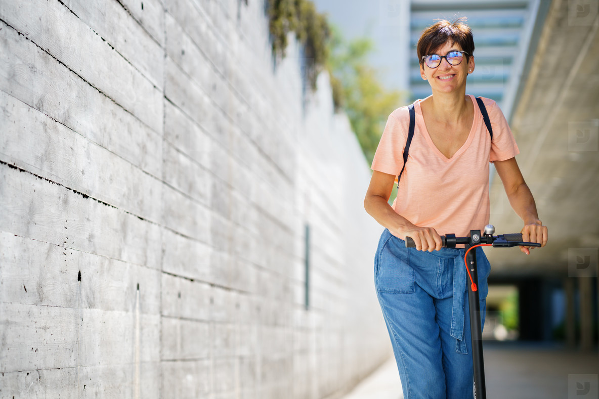 Woman riding around town on an electric scooter