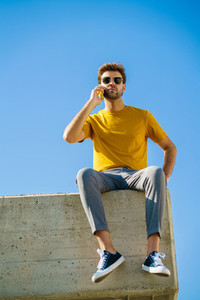 Young man using his smartphone sitting on a ledge outside