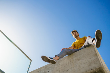 Man sitting on a ledge looking around