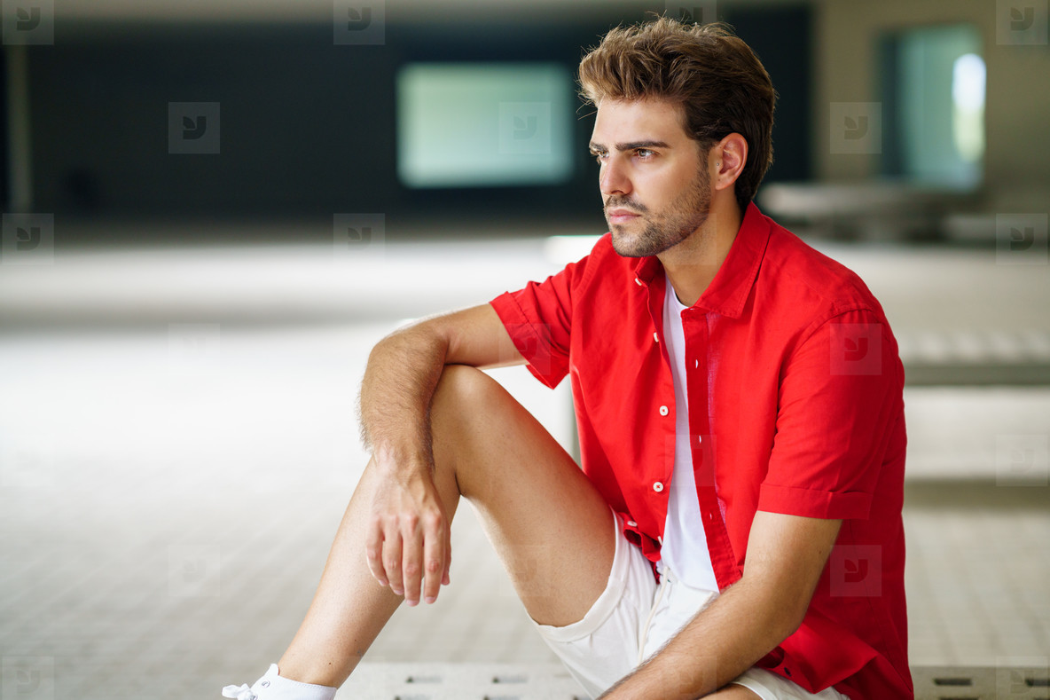 Male student sitting on a college campus bench