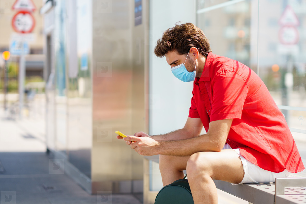 Young man wearing a surgical mask while waiting for a train at an outside station