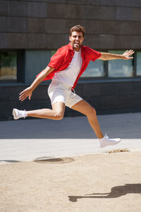 Man wearing casual clothes jumping in urban background