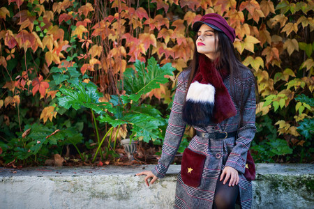 beautiful girl with very long hair wearing winter coat and cap in autumn leaves background