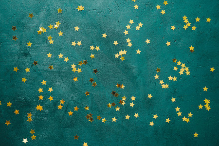 The New Year or Christmas festive flat lay with golden stars over a dark green background  Top view