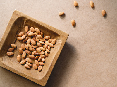 Almond nuts on a wooden handmade plate over a kraft paper background  Flat lay  top view