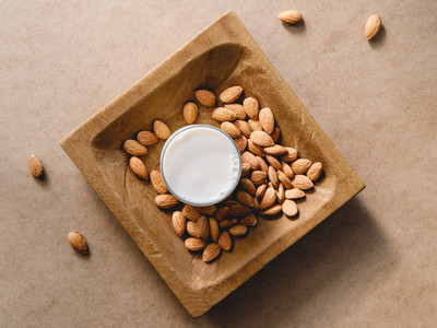Almond nuts on a wooden handmade plate and vegetarian plant milk over a kraft paper background Flat lay top view