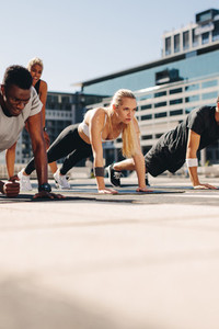 Healthy people doing core workout outdoors