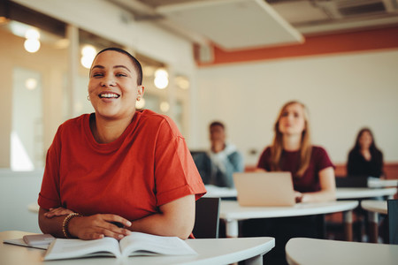 Smiling female student sitting in university classroom