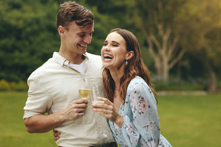 Beautiful couple in love with champagne at park