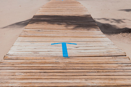 Symbol of an arrow on the wooden walkway in indicating the entrance to the beach
