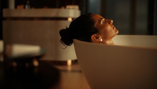 Woman lying in bathtub