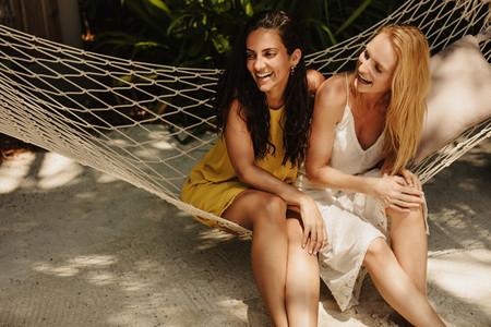 Women sitting in hammock having fun