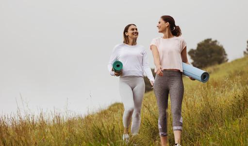 Women on a morning walk holding yoga mats